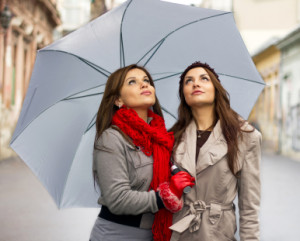 Beautiful young women with umbrella on rainy day .